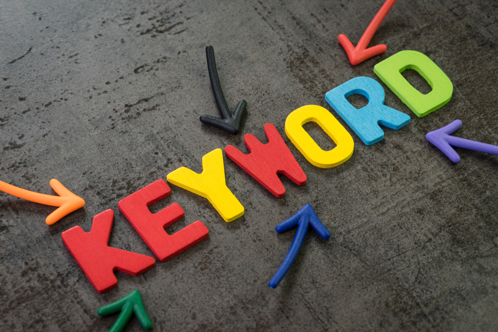 Keywords research for SEO, Search Engine Optimization, bidding on search result page to promote website online, multi color arrows pointing to the word Keyword at the center of black chalkboard wall.